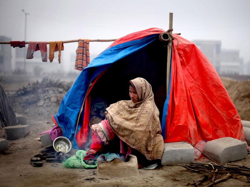 A construction worker keeps her child under a shawl as she sits outside her makeshift tent on a cold morning in New Delhi. AP/Altaf Qadri