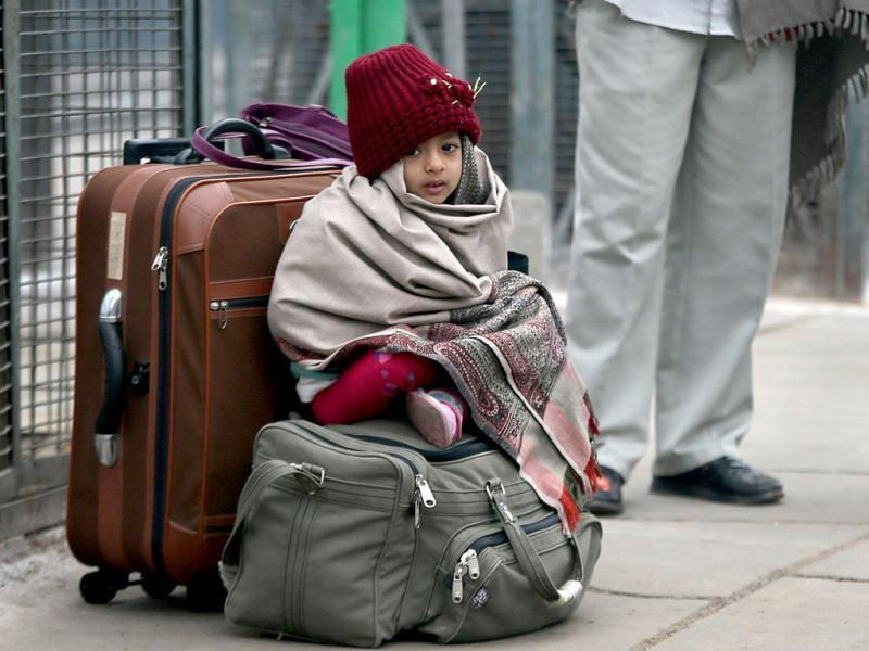 A girl sits on her luggage as she with her parents, unseen, waits for a train at a railway station in New Delhi. AP/Manish Swarup