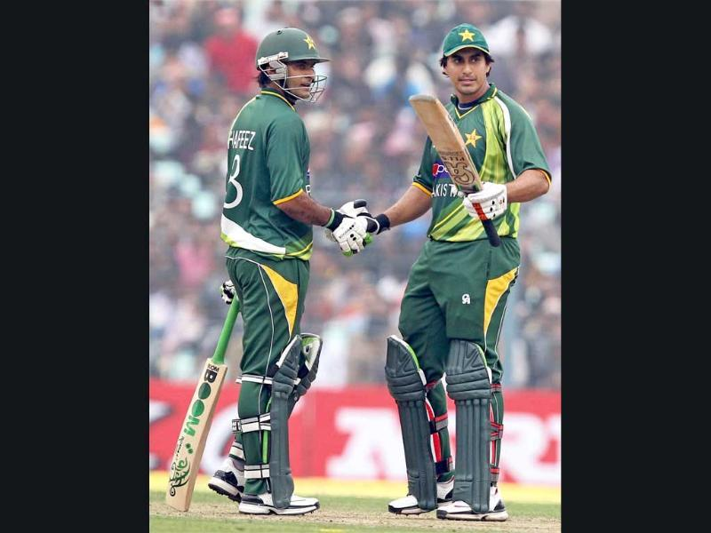 Pakistan's N Jamshed is greeted by M Hafeez for his half-century during the second ODI cricket match against India at Eden Garden in Kolkata . PTI/Ashok Bhaumik