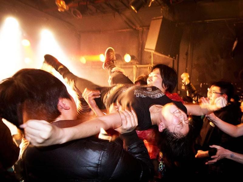 A crowd-surfer during a performance by rock band Demerit at the Mao Livehouse music venue in Beijing. AFP/Ed Jones