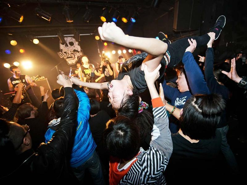 A crowd-surfer during a performance by punk band Demerit at the Mao Livehouse music venue in Beijing. Independent music acts in Beijing continue to pack out the city's many 'livehouse' venues where ear-splitting bands and hard-rocking fans represent a flourishing underground live music scene. AFP/Ed Jones
