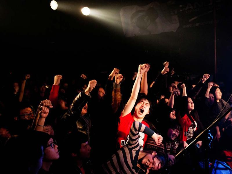 Members of the audience pumping their firsts into the air during a performance by punk band Demerit at the Mao Livehouse music venue in Beijing. AFP/Ed Jones