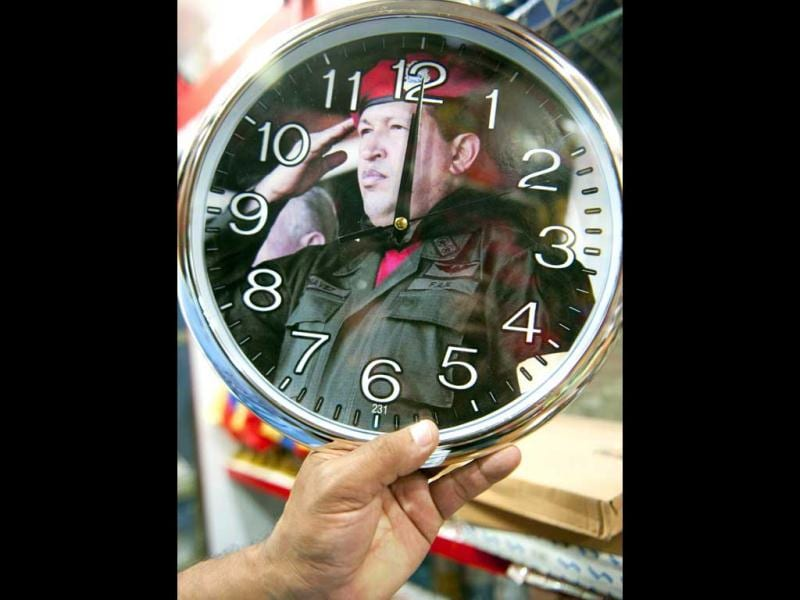 A man shows a clock with the image of Venezuelan President Hugo Chavez at a store in Caracas. AFP Photo