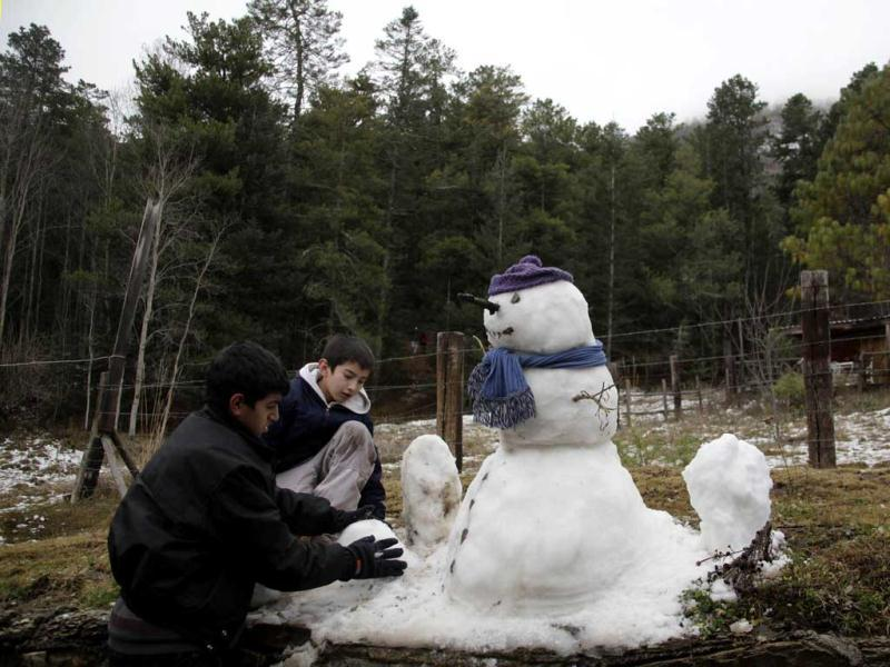 Children build a snowman after snow fell overnight at the Sierra de Arteaga, in the Mexican state of Coahuila. Reuters