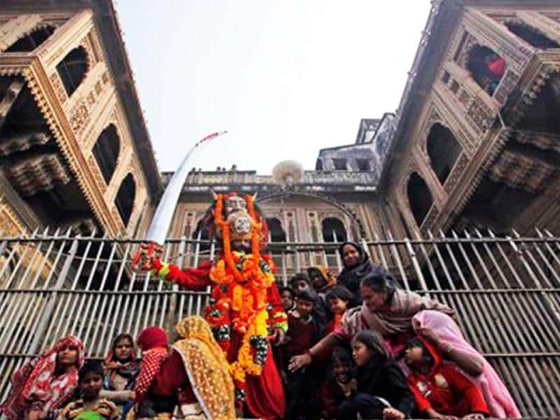 A man, dressed as a Sadhu, joins others as they watch a religious procession by Naga Sadhus towards the Sangam ahead of Maha Kumbh Mela that begins at Allahabad Jan 14. (AP Photo)