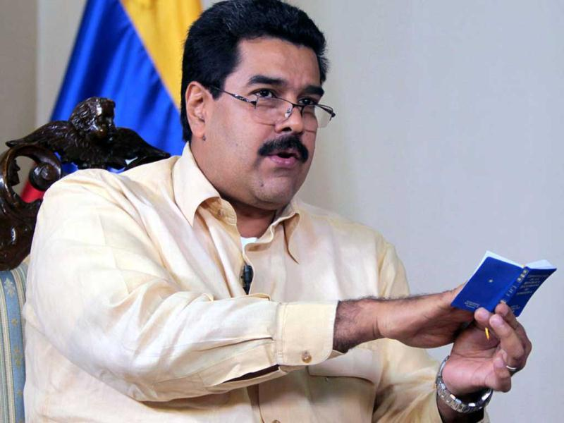 In this photo released by the Venezuelan Presidency of Venezuelan, vice president Nicolas Maduro as he speaks showing a Venezuelan Constitution book during a TV program in Caracas. AFP Photo