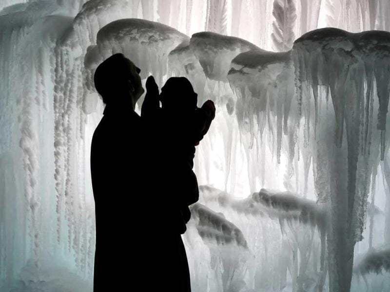 A man and his child explore the Mall of America Ice Castle in Bloomington, Minn. The castle is made of icicles organically grown from four million gallons of water and then fused together. AP Photo