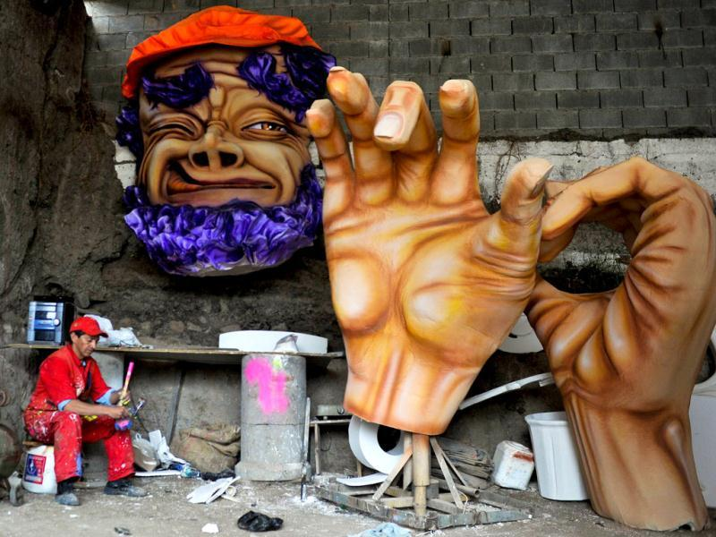 A craftsman sits next to parts of a float for the
