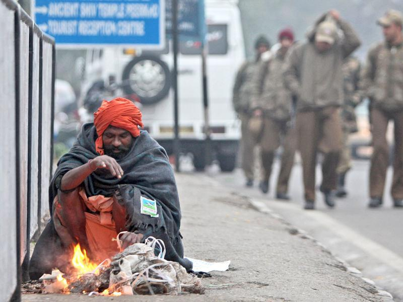 A sadhu keeps himself warm near a bonfire on a cold and foggy morning in Jammu. AP/Channi Anand