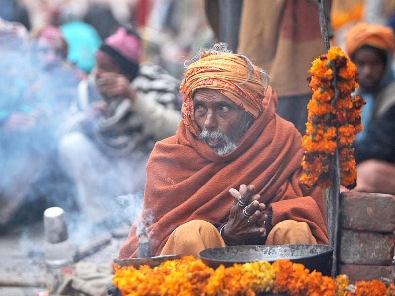 A sadhu sits near a bonfire to keep himself warm on a cold morning in Jammu. AP/Channi Anand