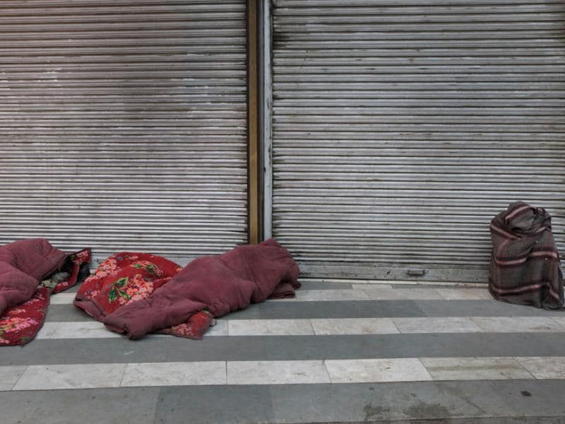 Homeless people sleep wrapped in quilts as another sits wrapped in a blanket in New Delhi. AP/Manish Swarup