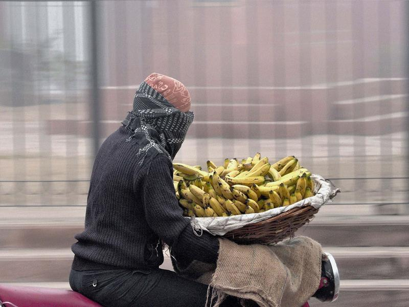 A vendor, wrapped in woollens, carries a fruit basket on his motorcycle during a cold foggy day in Bikaner. PTI