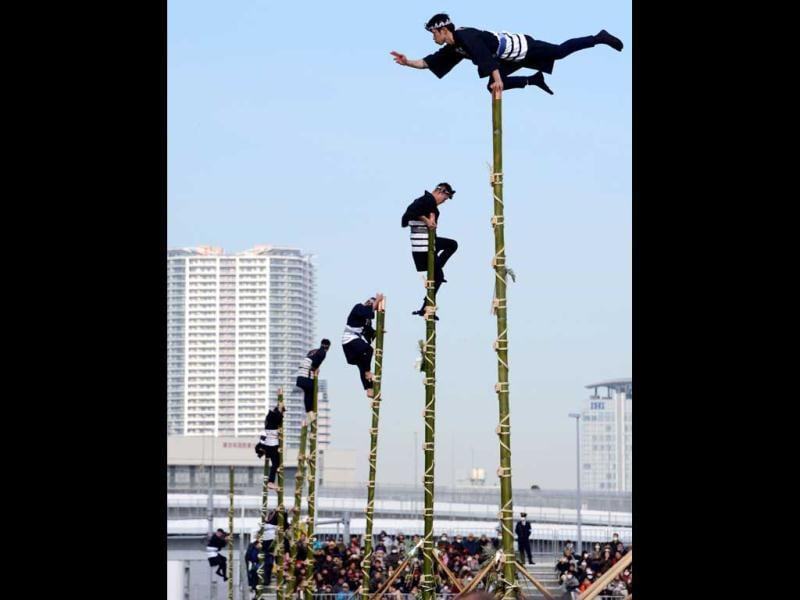 Members of the Edo Firemanship Preservation Association display their skills with stunts on the top of bamboo ladders at the annual new year fire review in Tokyo. AFP Photo