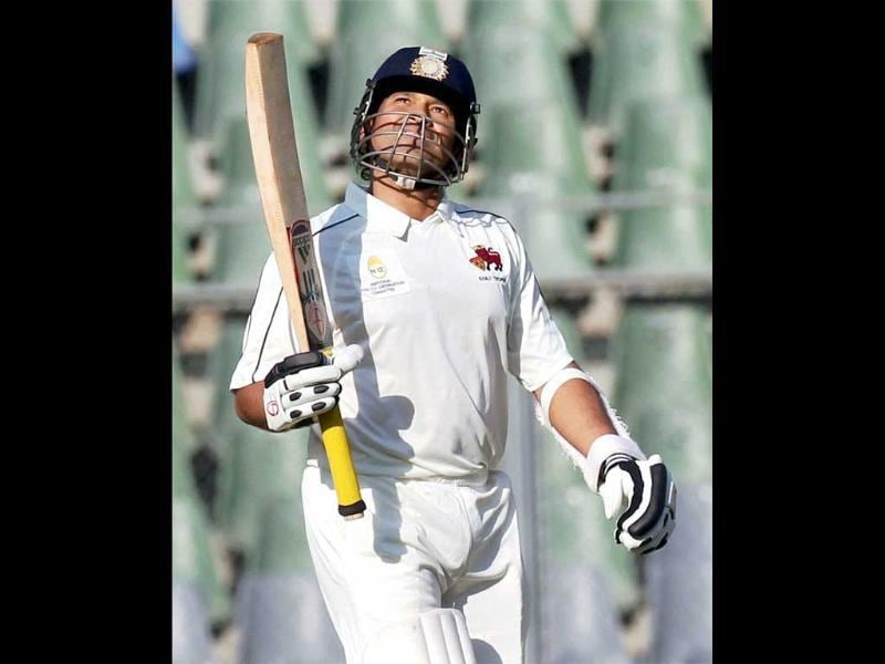 Sachin Tendulkar raises his bat after scoring a century against Baroda during the Ranji quarterfinal match in Mumbai. PTI/Shirish Shete