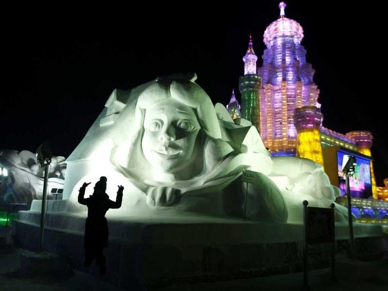 The picture shows a visitor posing before a snow sculpture in Ice and Snow World at the opening ceremony of the 2013 Harbin International Ice and Snow Festival in Harbin, in northeast China's Heilongjiang province. (AFP Photo)