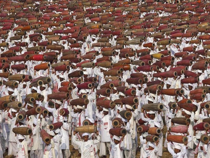 People wearing traditional Assamese attire raise their khol, a traditional percussion instrument of Assam, as they participate in an attempt to create a Guinness record, in Titabar, about 350 kilometers east of Guwahati. AP/Anupam Nath
