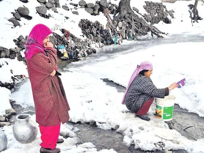 A woman fills her bucket with water from a partially frozen canal at Anantnag in Jammu and Kashmir on Sunday. PTI photo