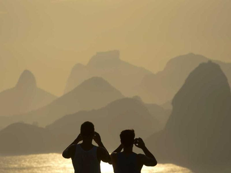 People photograph the sunset in Rio de Janeiro, Brazil, Sunday. (AP Photo)