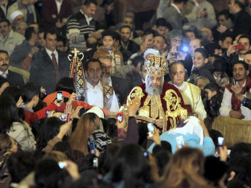 Pope Tawadros II, the 118th pope of the Coptic Church of Egypt, is greeted by Egyptian Christians as he prepares to lead a midnight Mass on the eve of Egyptian Orthodox Christmas at St. Mark's Cathedral in Cairo, Egypt. (AP Photo)