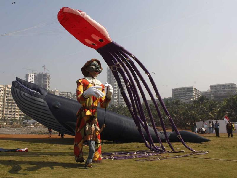 Participants fly a large kite at the International Kite Festival on the lawns of Priyadarshani park in Mumbai. Kite-flyers from different countries participated in the day-long festival. HT/Kunal Patil
