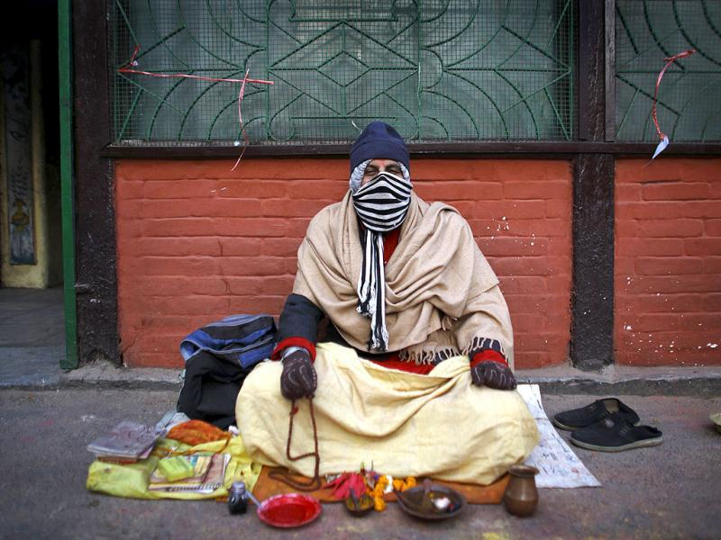 A priest covers himself with cloths to keep warm as he recites prayer outside a temple during a cold winter morning in Kathmandu. Reuters photo