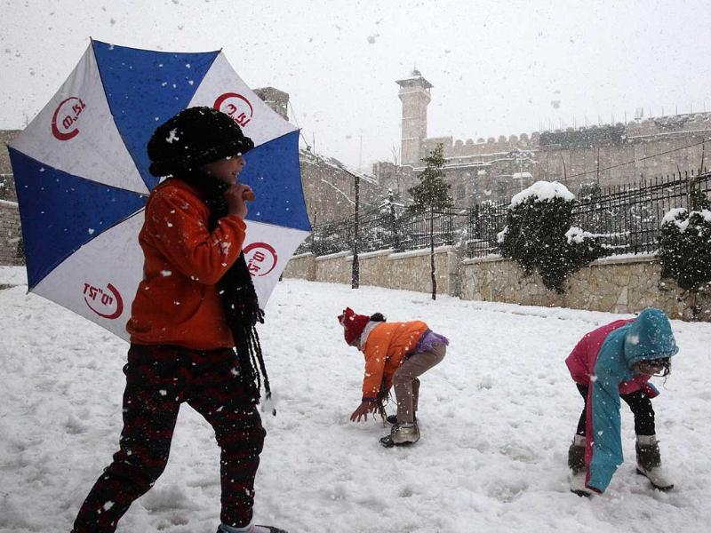Kids play with the snow in front of the Ibrahimi Mosque or the Tomb of the Patriarchs in the West Bank city of Hebron. AFP/Hazem Bader