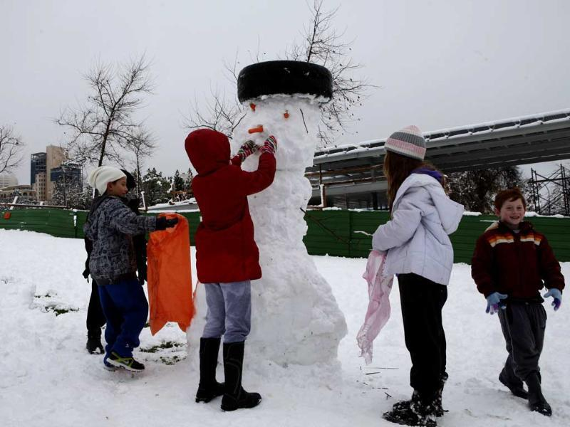 Children build a snowman at a park in Jerusalem. Jerusalem was transformed after heavy overnight snowfall turned the Holy City and much of the region white, bringing hordes of excited children onto the streets. AFP/Gali Tibbon