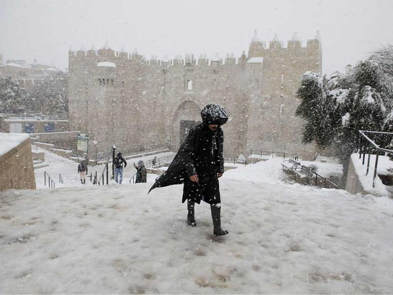 A man walks during a snow storm at Damascus Gate in the old city of Jerusalem. AFP/Gali Tibbon