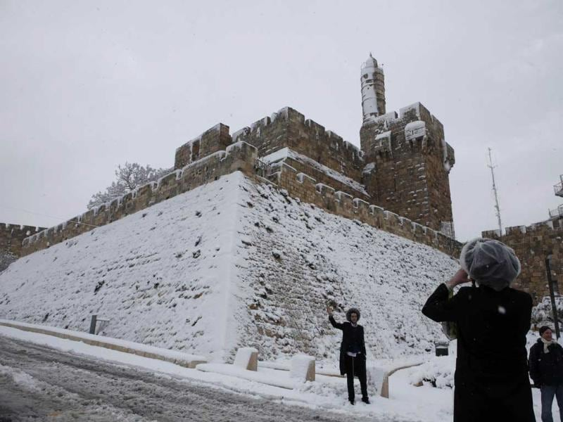 A Jewish man poses for a picture outside the snow-covered David's Tower in Jerusalem's old city. AFP/Gali Tibbon