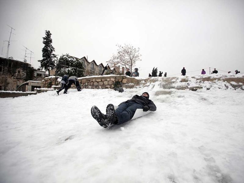 A Palestinian man slides on snow in the old city of Jerusalem. AFP/Ahmad Gharabli