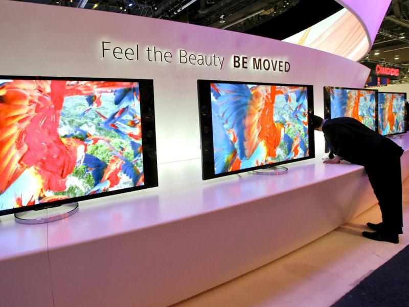 Vito Anzalone, far right, looks at the back of Sony's 4K XBR LED televisions at the Sony booth during a news conference at the International Consumer Electronics Show in Las Vegas. AP Photo