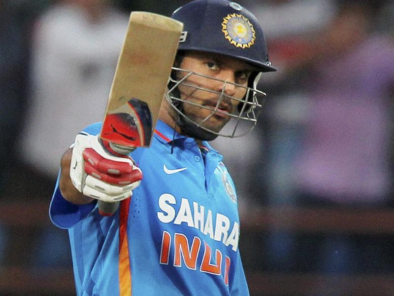 Yuvraj Singh raises his bat after his half century during the first ODI cricket match against England in Rajkot. PTI/Shirish Shete