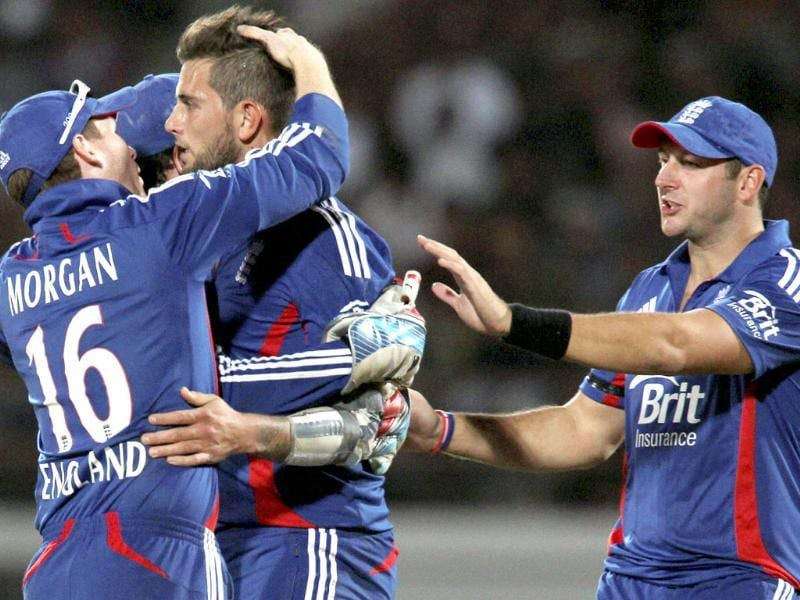 England's JW Dernbach celebrates with teammates after taking the wicket of M S Dhoni during the first ODI cricket match in Rajkot. PTI/Shirish Shete