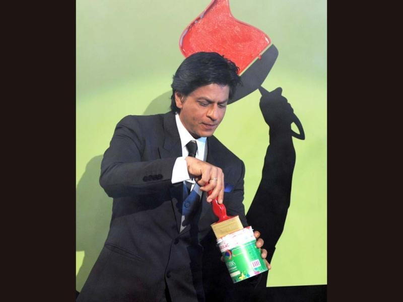 Shah Rukh Khan paints the wall red at the event.