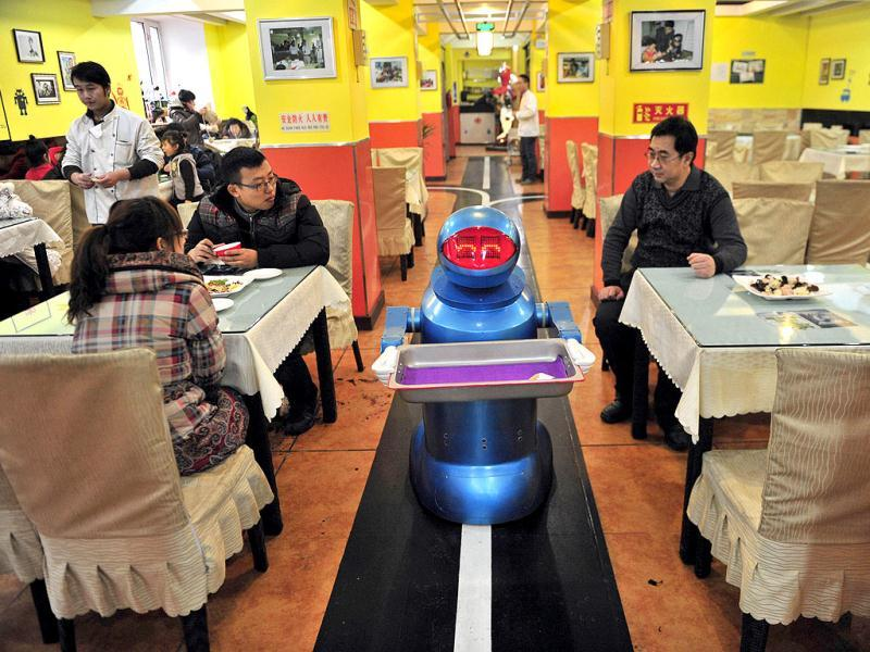 A robot that specialises in delivering food holds an empty plate after serving meals to customers at a Robot Restaurant in Harbin. Reuters Photo