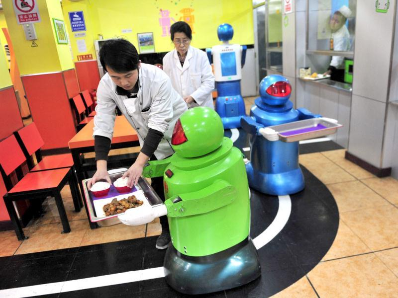 A robot that specialises in delivering food holds a tray as a waiter puts dishes on it at a Robot Restaurant in Harbin. Reuters