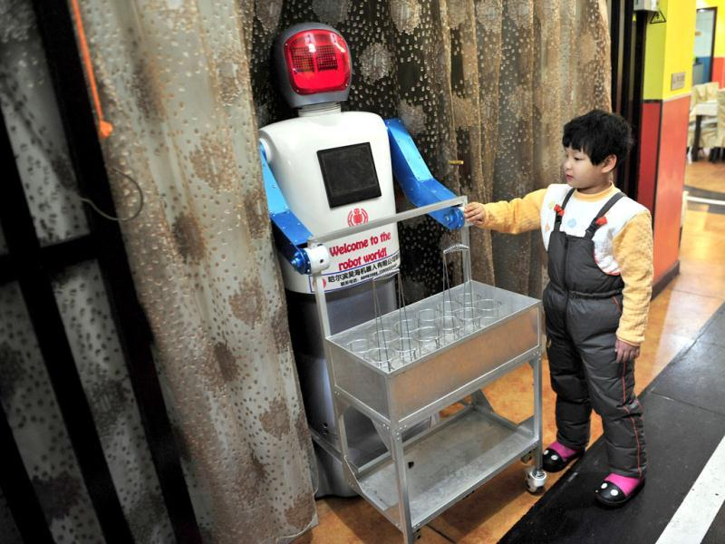 A boy touches a robot that specialises in delivering drinks at a Robot Restaurant in Harbin. Reuters