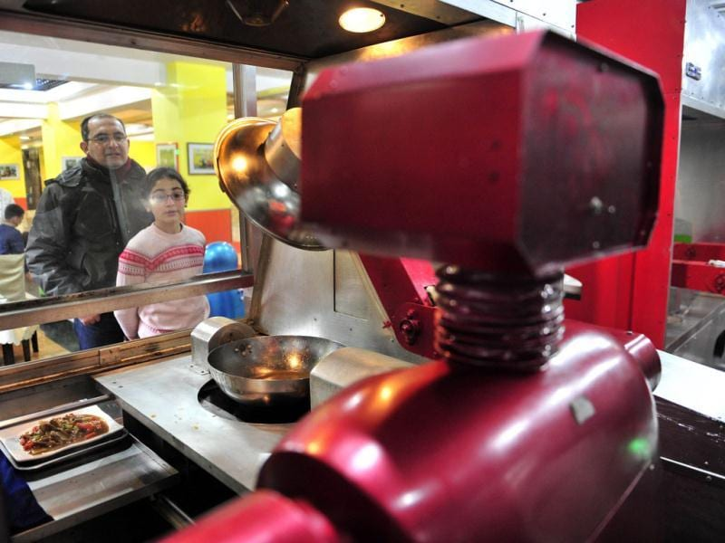 Customers watch a robot cooking dishes at a Robot Restaurant in Harbin. The robots can work continuously for five hours after a two-hour charge, and are able to display over 10 expressions on their faces and say basic welcoming sentences to customers, local media reported. Reuters Photo