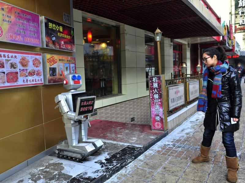 A pedestrian looks at a robot that specialises in greeting people outside a Robot Restaurant in Harbin, Heilongjiang province. The sign the robot is holding reads,