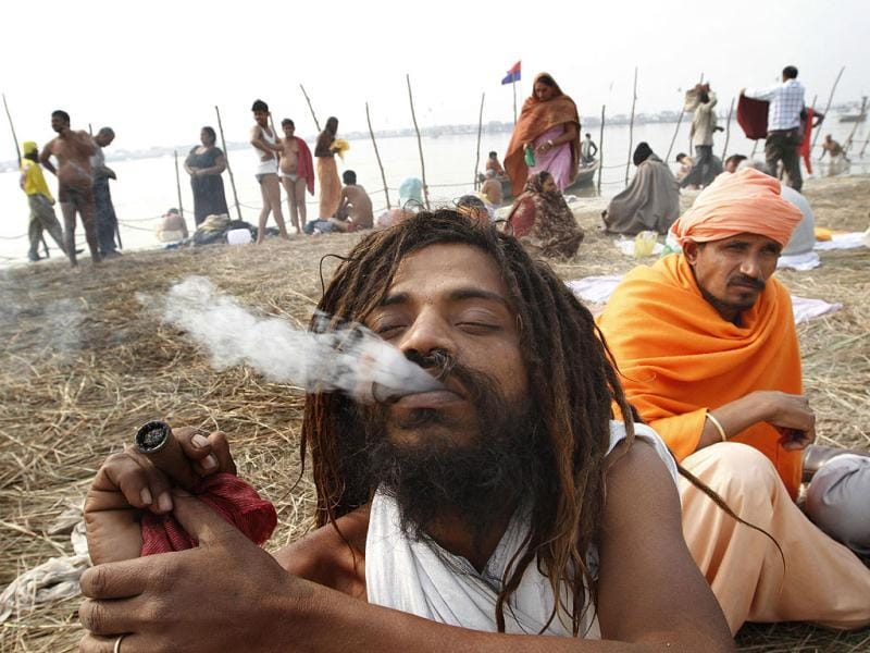 A Sadhu smokes at bank of Sangam ahead of Maha Kumbh Mela (festival), in Allahabad. Photo by Arvind Yadav/ Hindustan Times