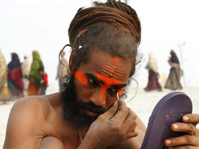 A sadhu applies colour on his face at the bank of Sangam ahead of Maha Kumbh Mela (festival), in Allahabad. Photo by Arvind Yadav/Hindustan Times