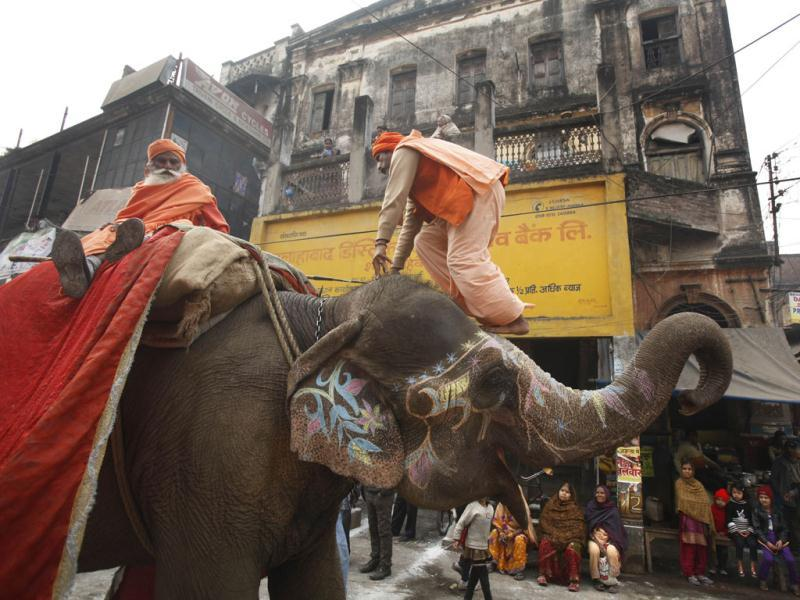 A sadhu climbs on an elephant during a religious procession towards the Sangam, the confluence of rivers Ganges, Yamuna and mythical Saraswati, as part of the Maha Kumbh festival, in Allahabad. Millions of Hindu pilgrims are expected to take part in the large religious congregation of a period of over a month on the banks of Sangam during the Maha Kumbh festival in January 2013, which falls every 12th year. (AP Photo/Rajesh Kumar Singh)
