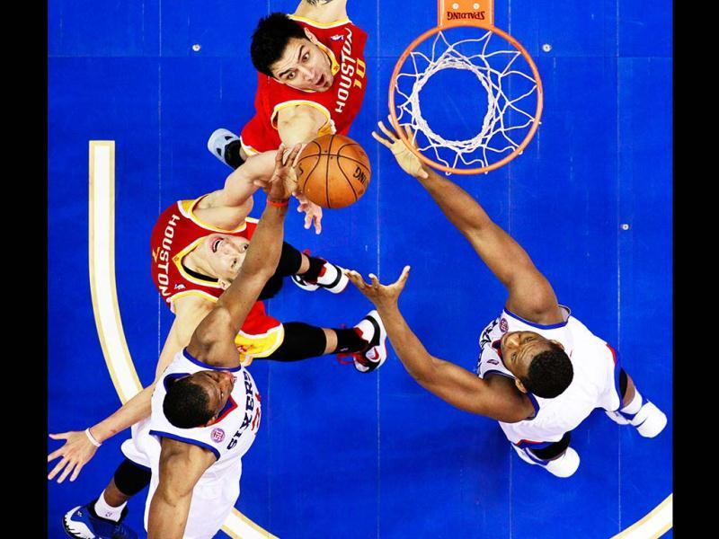 Houston Rockets' Carlos Delfino, of Argentina and Jeremy Lin leap for a rebound against Philadelphia 76ers' Thaddeus Young, left, and Lavoy Allen in the second half of an NBA basketball game in Philadelphia. AP Photo