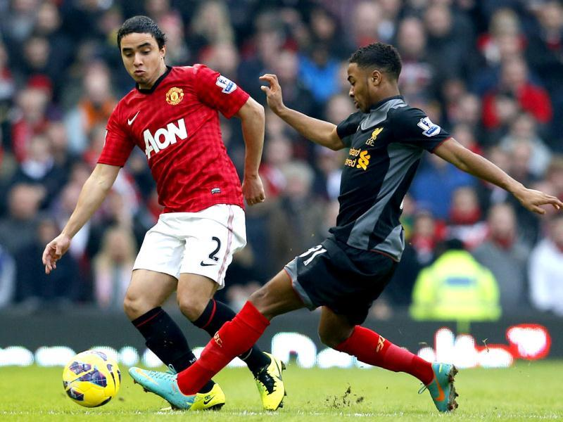 Manchester United's Rafael Da Silva challenges Liverpool's Raheem Sterling (R) during their English Premier League soccer match at Old Trafford in Manchester, northern England. Reuters
