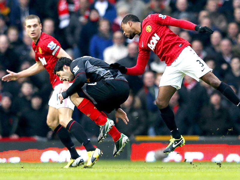 Manchester United's Patrice Evra (R) fouls Liverpool's Luis Suarez during their English Premier League soccer match at Old Trafford in Manchester, northern England. Reuters