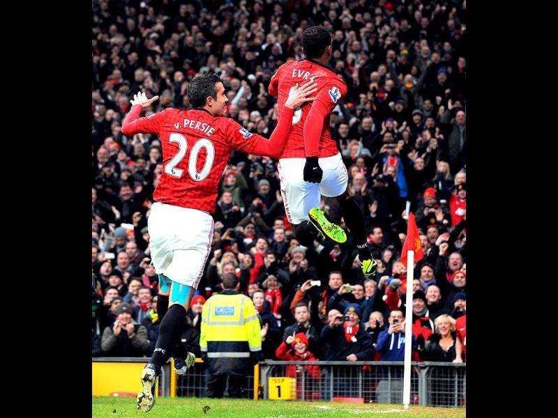 Manchester United's French defender Patrice Evra (R) and Manchester United's Dutch striker Robin van Persie (L) celebrate United's second goal during the English Premier League football match between Manchester United and Liverpool at Old Trafford in Manchester, northwest England, on January 13, 2013. AFP