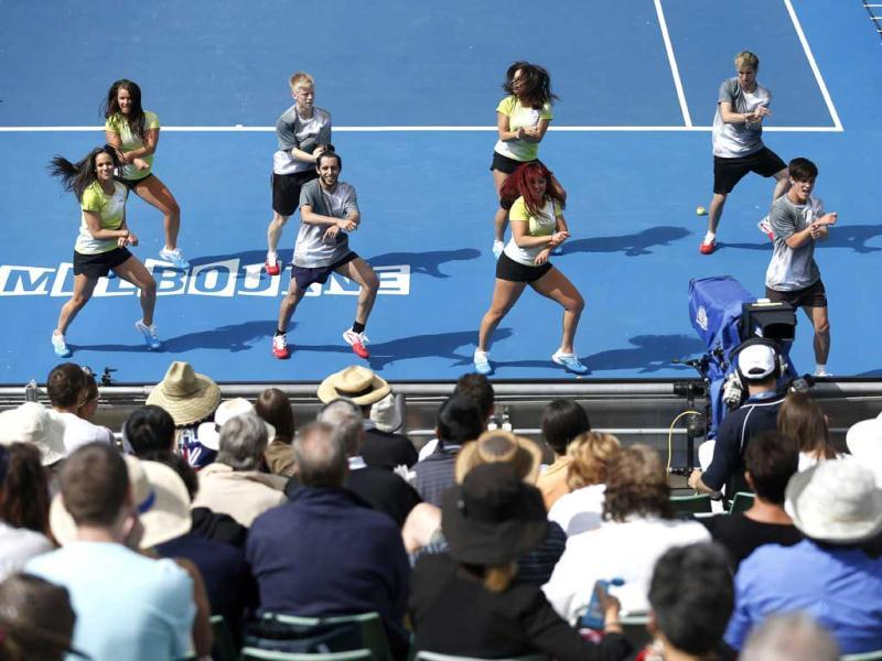 Entertainers perform the Gangnam Style dance on Margaret Court Arena during a break in the first round match between China's Li Na and Kazakstan's Sesil Karatantcheva at the Australian Open tennis championship in Melbourne, Australia. (AP Photo)