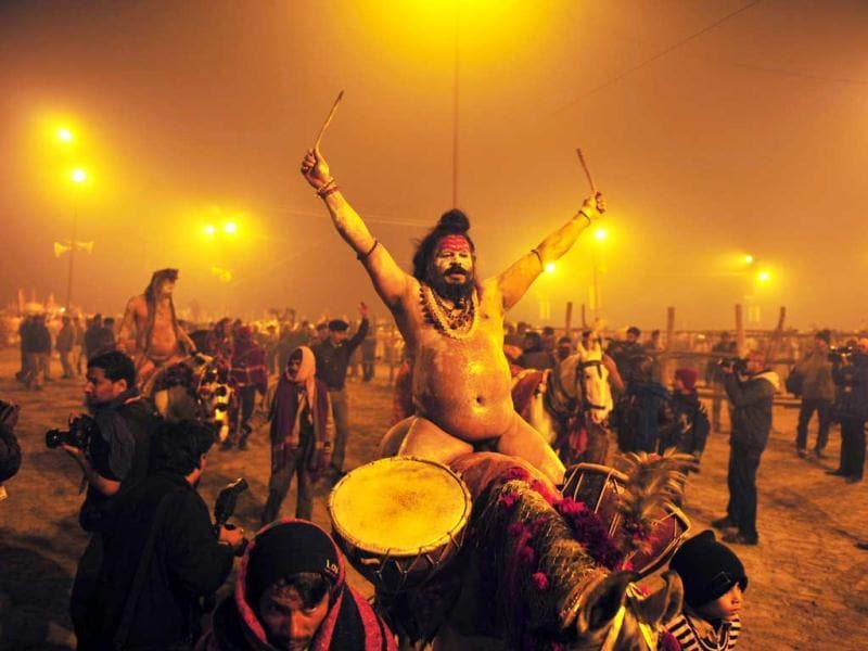 A sadhu beats on drums while riding a horse while he and others like him marched towards the Sangham in Allahabad. AFP/Sanjay Kanojia