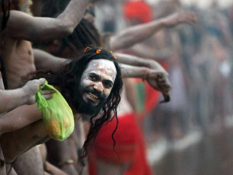 A Naga sadhu watches others as he waits for a dip at Sangam in Allahabad. AP/Manish Swarup