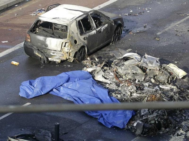 Remnants of a helicopter which crashed onto a construction crane is seen on the ground by a burnt out car in London. AP Photo